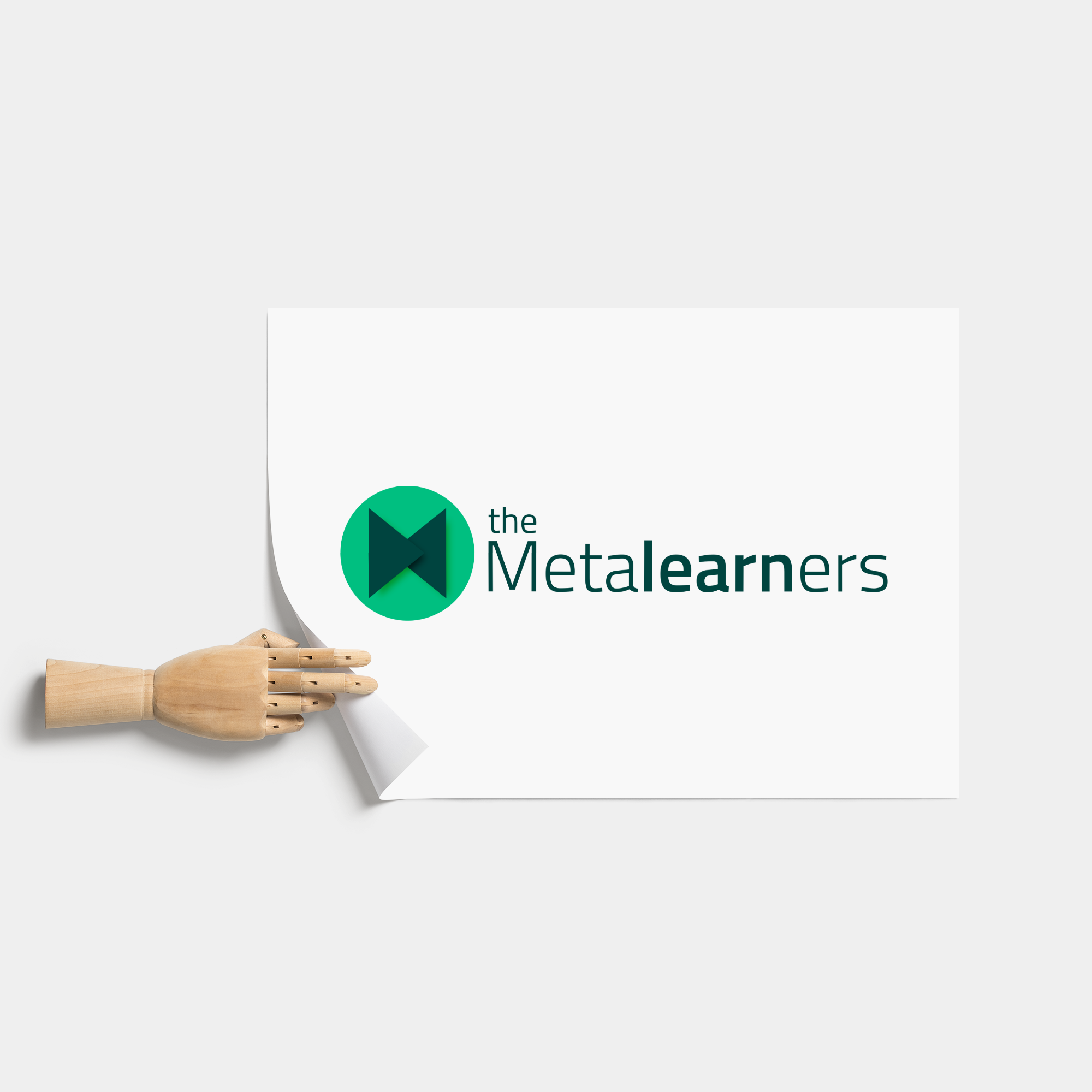 The Metalearners logo on an A4 sheet and a wooden hand